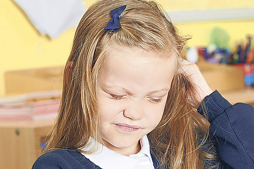 Ein blondes Mädchen mit langem Haar kratzt sich am Kopf, vielleicht hat sie Kopfläuse.