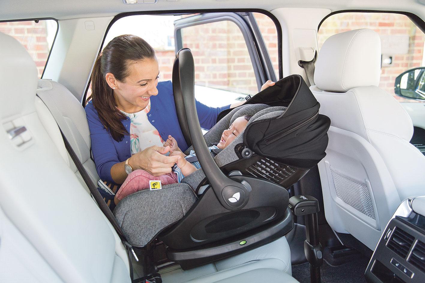 Mutter mit ihrem Kind im Auto. Das Baby liegt in einer Babyschale.