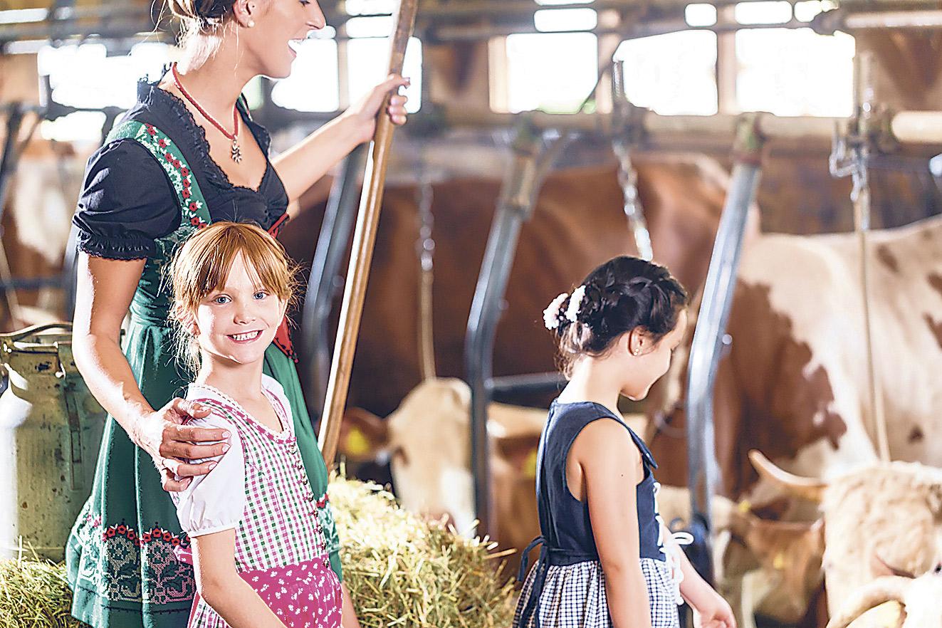 Zwei Mädchen mit einer Frau im Stall beim Besuch auf dem Bauernhof.
