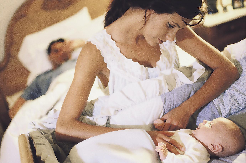 Eine Mutter steht an der Wiege ihres Neugeborenen und schaut, ob es schläft.