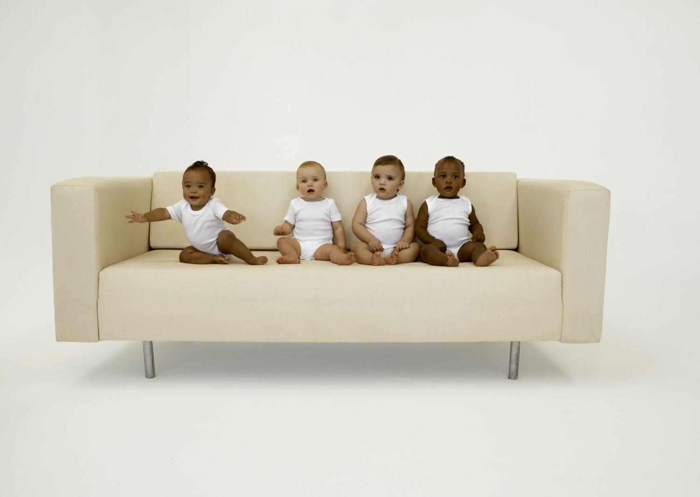 Vier Babys sitzen auf einer beigen Couch