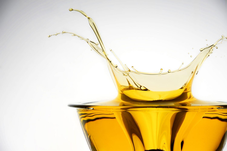 Ein Tropfen Olivenöl fällt in ein Glas Olivenöl.