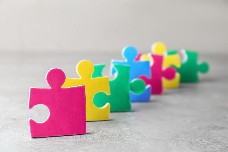 Bunte Puzzle-Stücke hintereinander aufgereiht