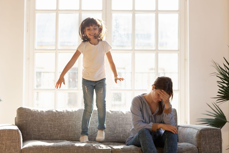 Tochter springt auf der Couch herum, während die Mutter verzweifelt daneben sitzt. Thema: ADHS bei Kindern