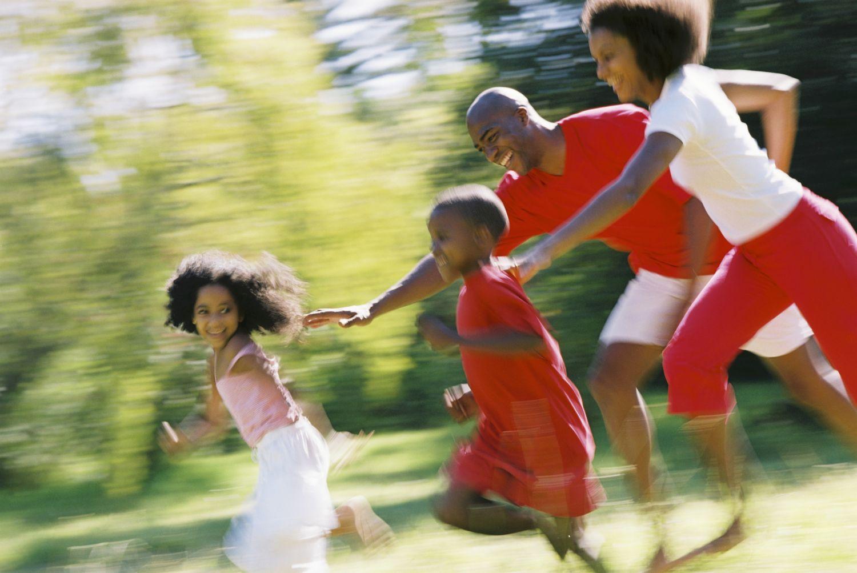 Kinder in Bewegung: Eltern spielen Fangen mit ihren Kindern