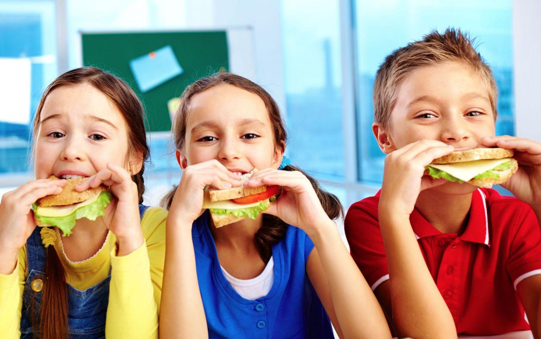 Drei Kinder essen Hamburger.