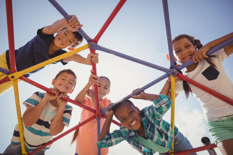 Kinder auf einem Klettergerüst. Thema: Das Geheimnis glücklicher Kinder