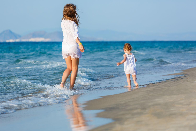 Thema: Sonnenschutz. Mutter spaziert mit Tochter den Strand entlang.