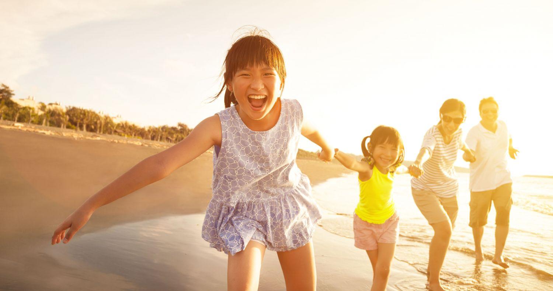 Eine glückliche Familie beim Strandspaziergang im Sonnenuntergang