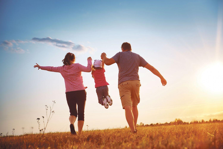 Mutter, Vater und Kind laufen Hand in Hand über ein Feld.