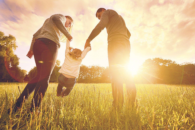Mutter und Vater halten im Sonnenuntergang ihr Kind an seinen Armen in die Höhe.