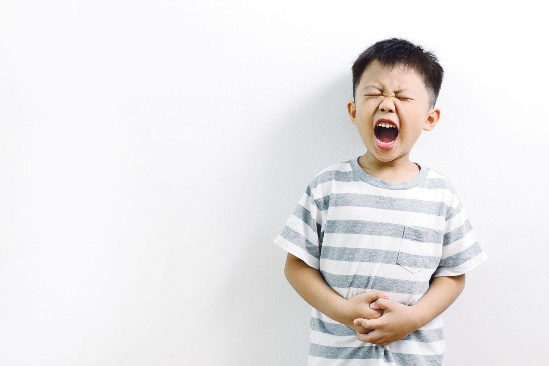 Schreiender Junge mit Bauchschmerzen. Thema: Darmflora