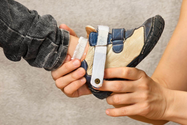 Mutter zieht Kind einen Schuh an